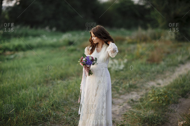 Bride walking with bouquet on rural path