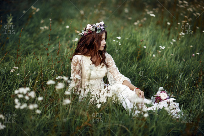 Bride sitting in grass wearing floral crown