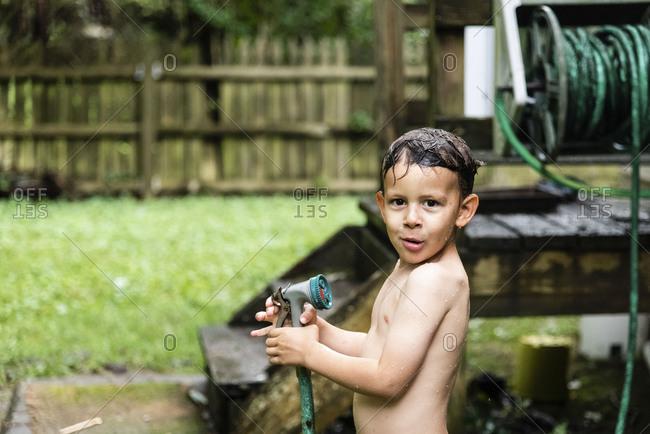 Soaking wet boy holding hose