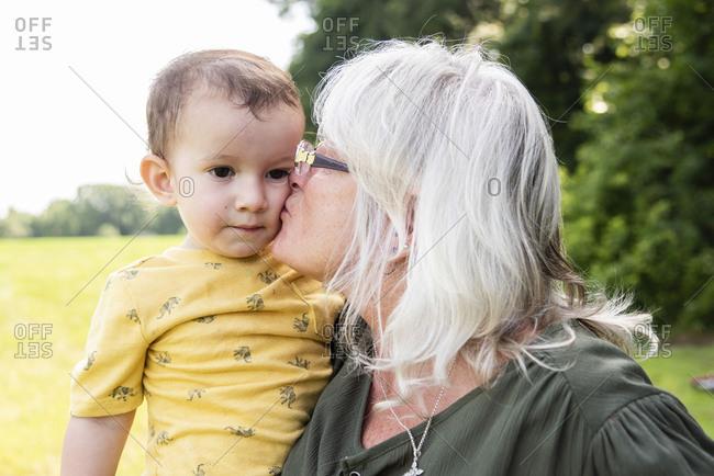 Grandmother kissing toddler boy outdoors