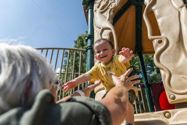Grandmother reaching for toddler boy on slide at park