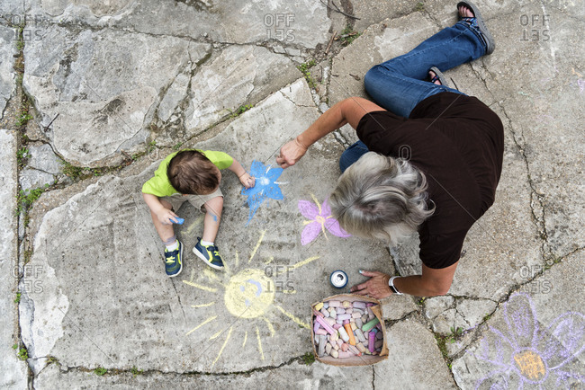 Grandmother and toddler boy drawing with sidewalk chalk