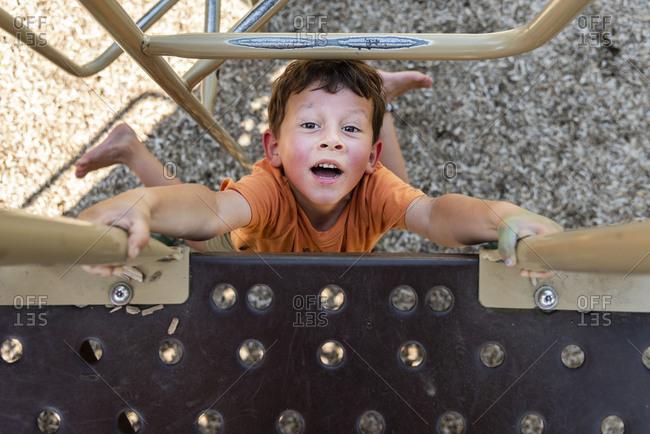 Overhead view of boy climbing on playground equipment