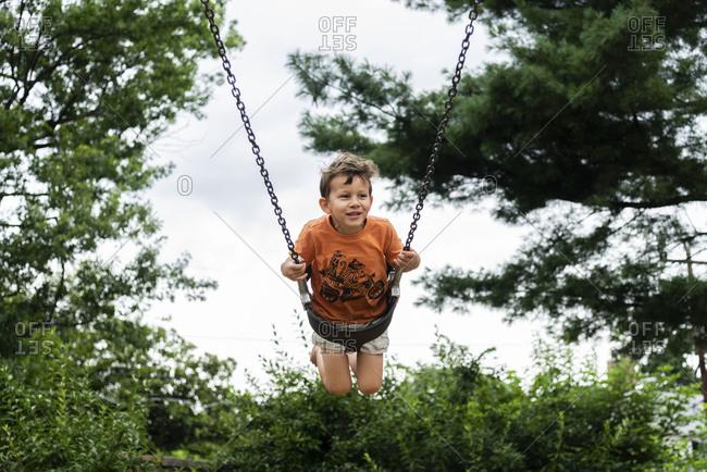 Happy boy on swing at park