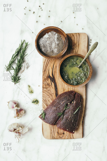 Beef, garlic, salt and rosemary on a marble surface