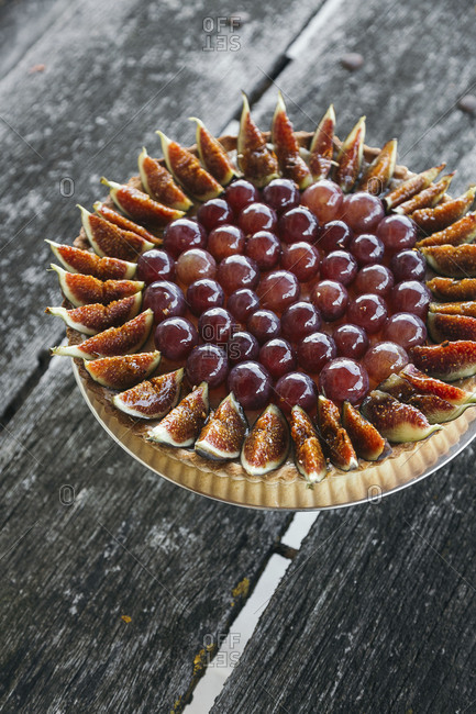 Fig and red grape tart on a wooden surface