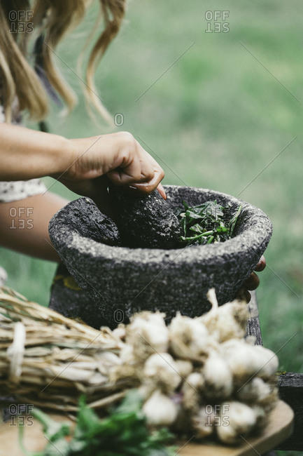 A girl making pesto in the garden