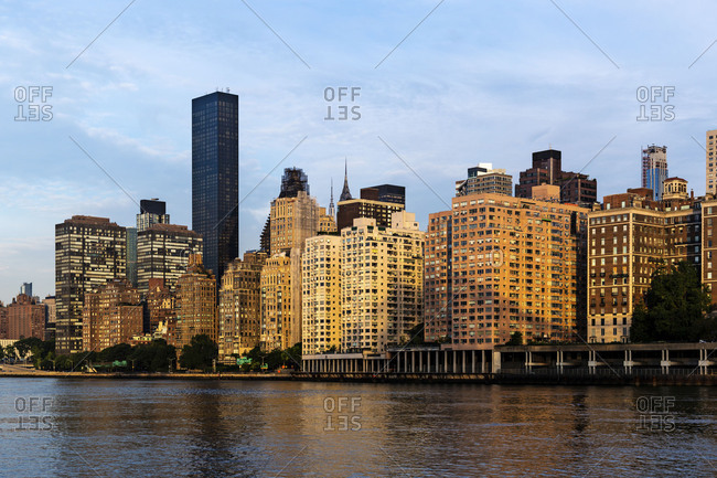 View of Midtown Manhattan buildings, skyscrapers and apartments from Roosevelt Island at sunrise