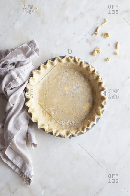 Pie crust with crimped edge on a marble work surface