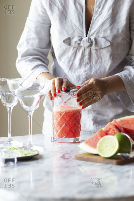 Woman making watermelon margaritas