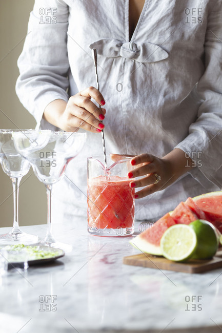 Woman stirring watermelon juice in pitcher to make margaritas
