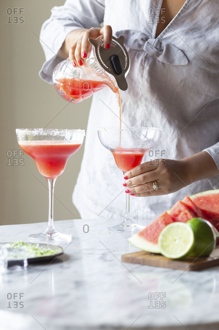 Woman pouring watermelon margarita drink from a pitcher into a cocktail glass