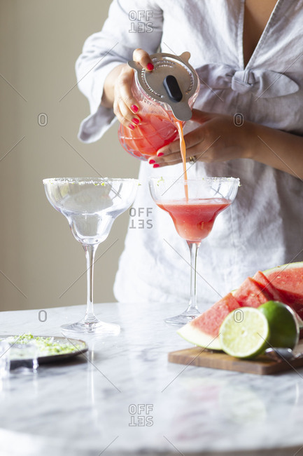 Woman pouring margarita drink from a pitcher into a glass