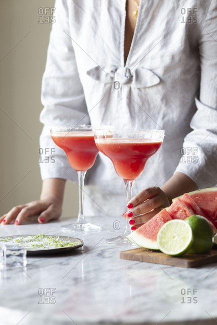 Woman with two freshly made watermelon margaritas served in glasses with salted rims