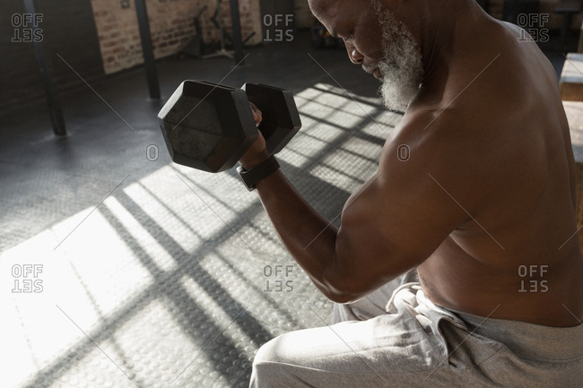 Close-up of determined senior man exercising with dumbbell in the fitness studio