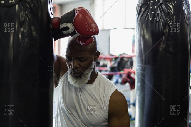 Close-up of tired senior boxer leaning against the punching bag