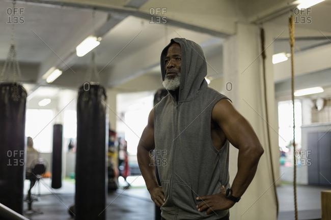 Determined senior man in hooded sweatshirt standing in the fitness studio
