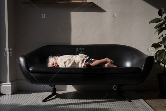 Baby girl sleeping on sofa in living room at home