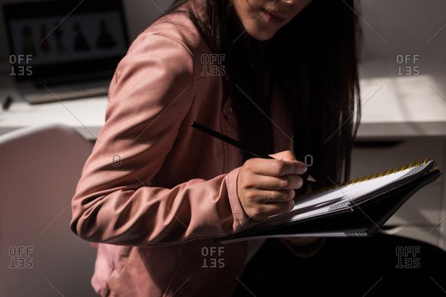 Mid section of fashion designer making sketch in the design studio