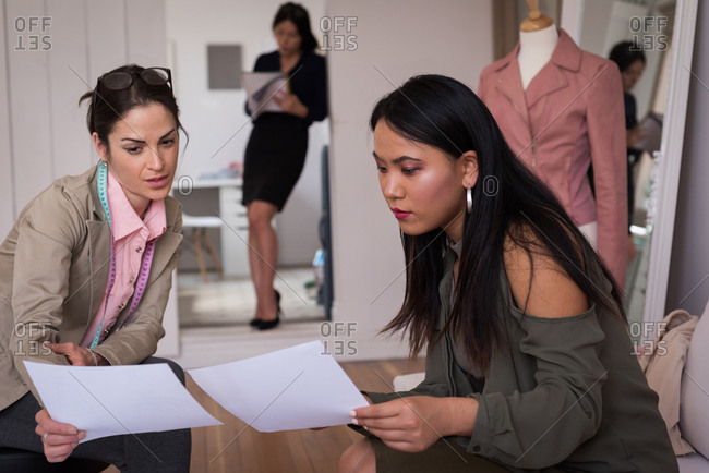 Fashion designers discussing over the sketches in the studio