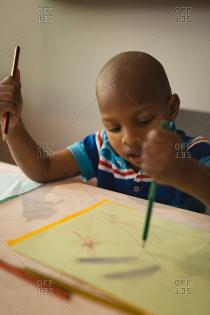 Innocent boy drawing a sketch at home