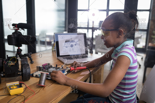 Teenage blogger soldering a circuit board in office
