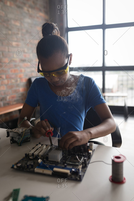 Girl soldering a circuit board at desk in office