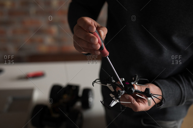 Mid section of male electrical engineer repairing a drone