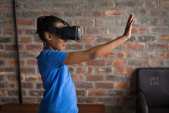Innocent girl using virtual reality headset in office