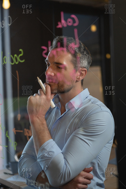 Thoughtful  executive reading notes on the glass wall in office