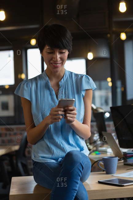 Smiling female executive using mobile phone at desk in office