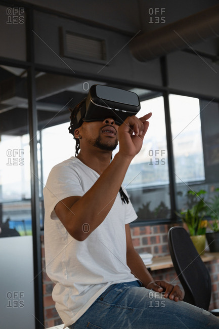 Excited man experiencing virtual reality in office