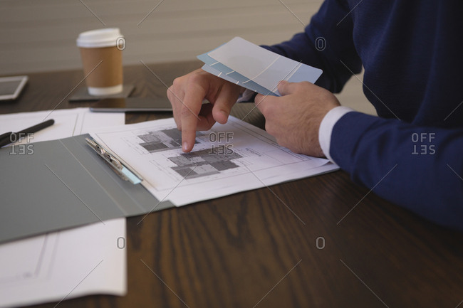 Mid section of businessman discussing blueprint at office
