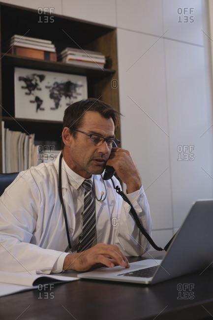 Doctor talking on landline while using laptop in office