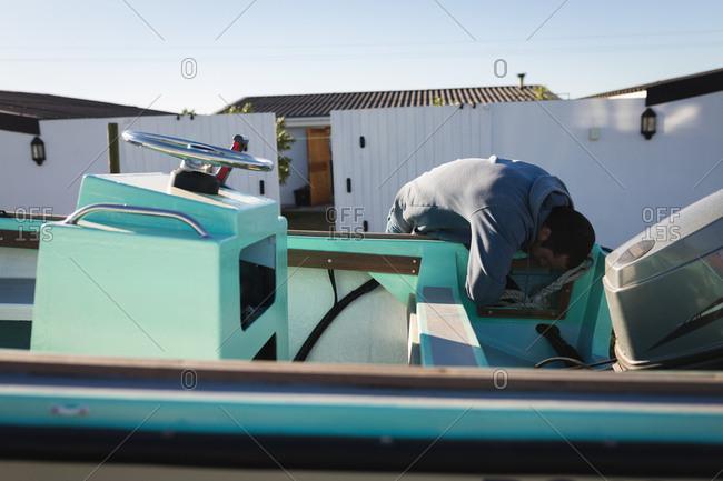 Man checking motor boat in the backyard