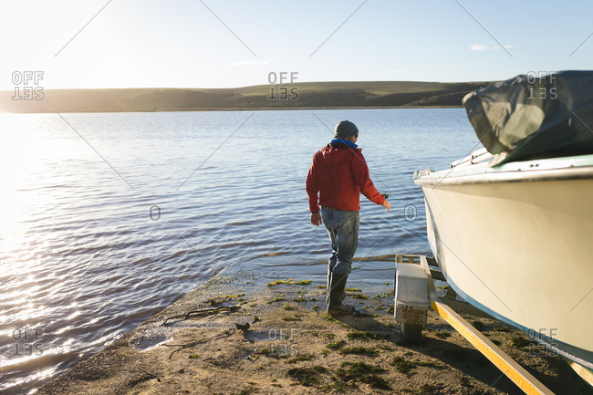 Man checking motorboat near river side
