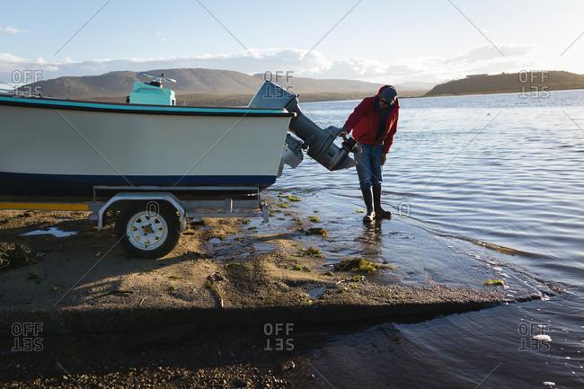 Man checking motor boat near river side
