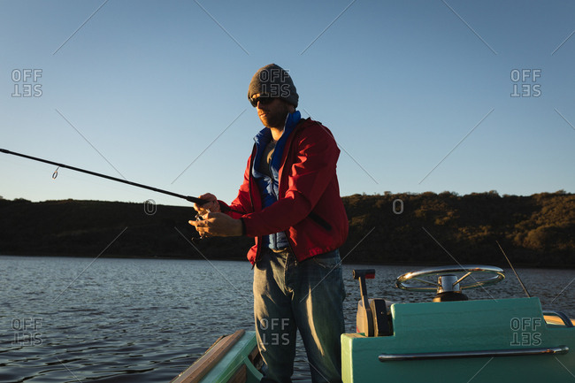 Man fishing while standing on motorboat in river