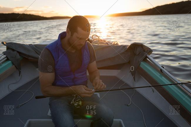 Attentive man tying fishing rod in motorboat