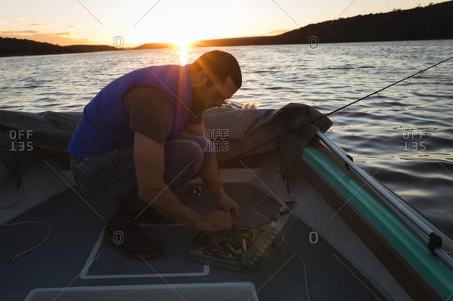 Man preparing bait for fishing on motorboat