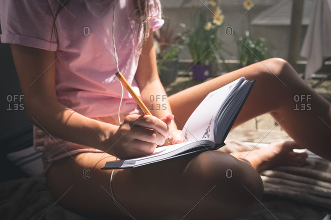 Close up view woman writing in diary at home