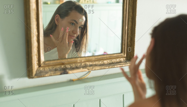 Woman applying face cream in front of mirror at home
