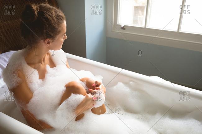 Woman taking a bath in bath tub at home