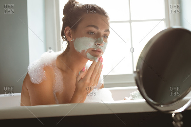 Woman applying facial mask while taking bath in bathroom at home
