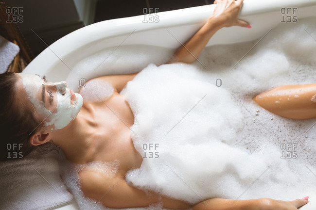 Woman applying face mask while taking bath at home