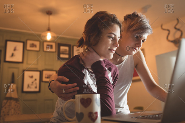 Lesbian couple using laptop in living room at home