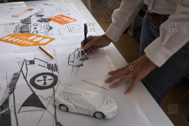 Mid section of businesswoman drawing car sketch in office