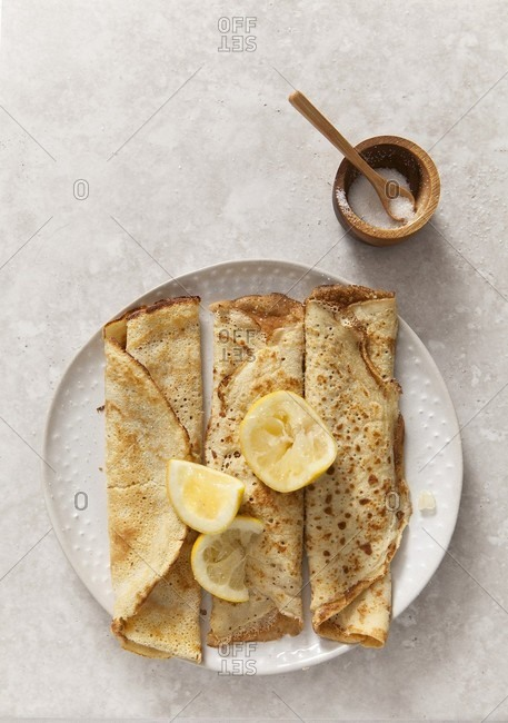three rolled pancakes on a off white texture plate with lemon wedges on a stone surface propped with wooden sugar bowl and spoon