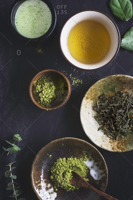 A cup of matcha latte, a cup of green tea, matcha powder in a small bowl and green tea on a dark background