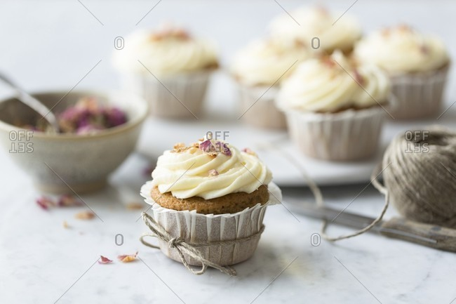 Rose and lemon cupcakes with rosewater and lemon frosting tied with string with spoon and bowl of rose petals on a white and grey marble surface